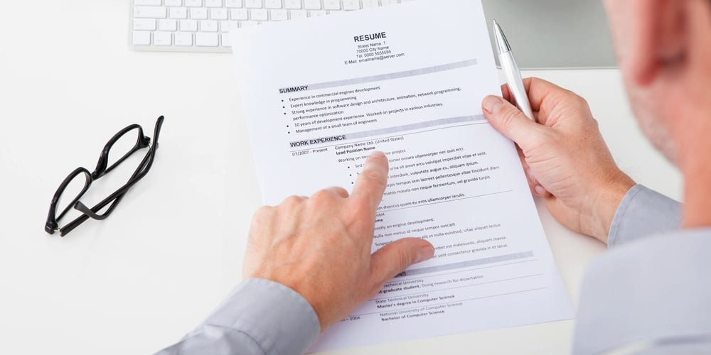 A man holding a printed resume, a glasses on the left of the table and on his right hand he holds a pen