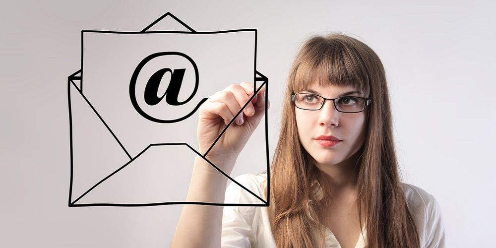 A girl drawing in front of her a letter with an email logo on a paper