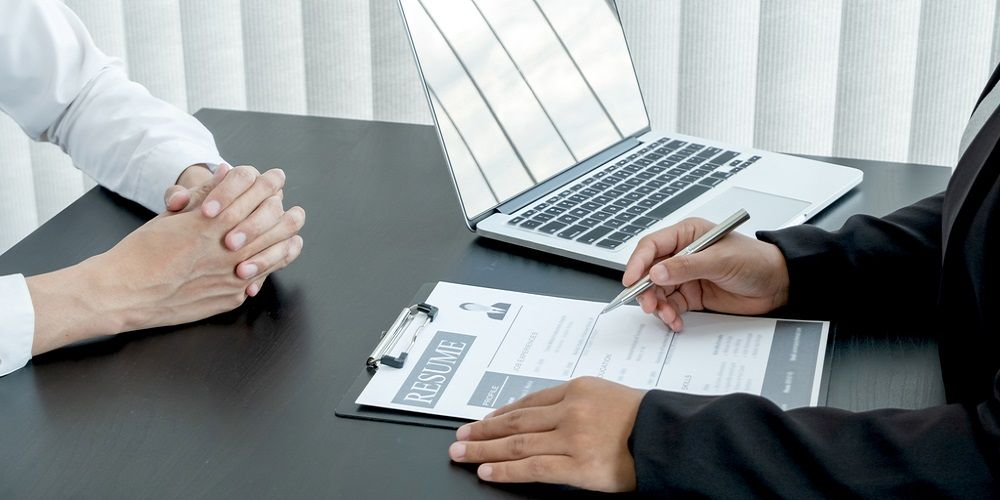 Two people with hands on the table and one of them has a resume and a laptop