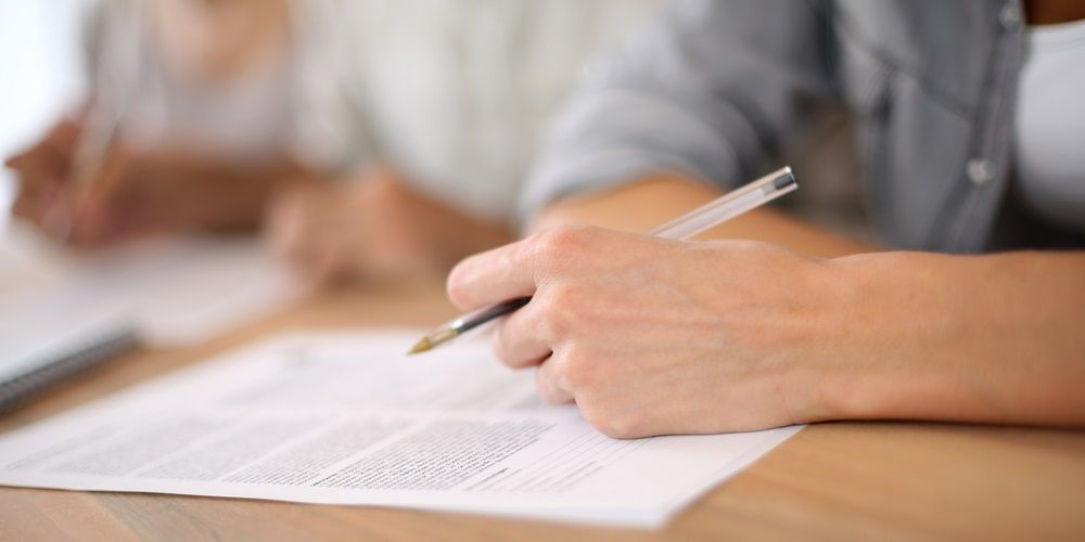 A men with a pen writing on a paper